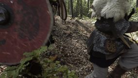 Vikings running in the forest to fight in a battle. Medieval Vikings running in the forest to fight in a battle. Vikings clad in chain mail, with shields, swords stock video footage