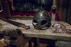 Vikingstol och tabell med den viking hjälmen och slåsssvärdet royaltyfri fotografi