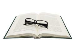 Vikt glasögon på den öppnade boken som isoleras på vit Royaltyfria Bilder