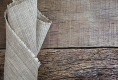 Vikt grå servett på en träbakgrund variation för textur för säck för diagram för fragment för torkduk för konstbakgrundsburlap Mo Arkivbild