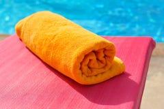 Vikt orange handduk på bakgrunden av pölen Royaltyfria Foton