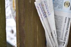 Vikt tidning som klämmas fast mellan posteringar av ett trästaket Royaltyfri Fotografi