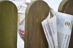 Vikt tidning som klämmas fast mellan posteringar av ett trästaket Arkivfoto