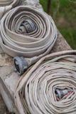 Vikta brandmän bevattnar slangar arkivbild