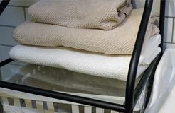 Vikta handdukar, matthäftklammermatare och badrockar på en hylla av en garderob i ett hotell arkivfoto