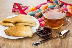 Vikta pannkakor i plattan, kopp te, körsbärsrött driftstopp Royaltyfri Foto