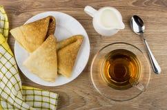 Vikta pannkakor i plattan, kopp te, tillbringare av mjölkar Arkivbild