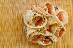 Vikta pannkakor med kaviaren som är ordnad artfully på en platta Royaltyfria Foton