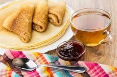 Vikta pannkakor på maträtten, te, körsbärsrött driftstopp i bunke Arkivbild