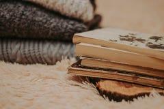 Vikta stack woolen tröjor, bunt av gamla böcker på en hemtrevlig fluffig beige filt arkivfoton