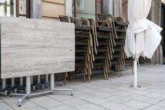 Vikta tabeller och stolar av en gatakaféställning på trottoaren royaltyfri bild