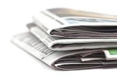 Vikta tidningar på vit bakgrund Arkivbilder