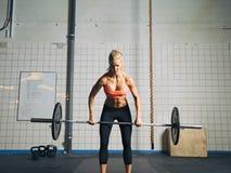 Vikter för Crossfit kvinnalyftande skurkroll i idrottshall Royaltyfri Fotografi