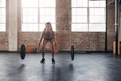 Vikter för Crossfit kvinnalyftande skurkroll i idrottshall Royaltyfria Bilder