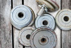 Vikter för konditionutrustninghantel på gammal wood bakgrund Arkivfoto