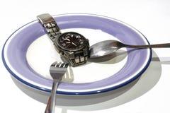 Viktförlust eller bantar begreppsmaterielbild av klockan på plattan Arkivfoto