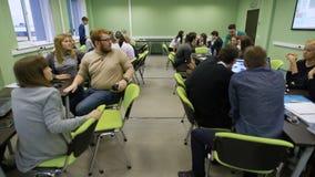 Viktig praktisk kurs i affärsskola Stort nummer avstudenter delade in i grupper som studerar information från stock video
