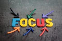 Viktigt av fokus, koncentration, avsikt i arbete eller livbegreppet, färgrika pilar som pekar till ordet FOKUS på mitten på fotografering för bildbyråer