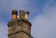 Viktorianischer inländischer Kamin mit vier sortierte Kamintöpfe gegen einen klaren Hintergrund des blauen Himmels Kopieren Sie P Stockbilder