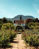Viktoriansk stilstuga med bågen i rosa trädgård royaltyfria foton