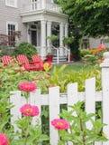 Viktorianskt hem med röda stolar i sommarträdgård Fotografering för Bildbyråer