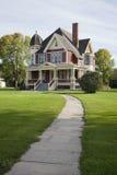 Viktorianskt hus med gräsmatta och trottoaren på solig eftermiddag Arkivfoton