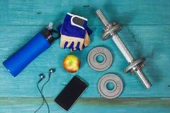 Viktplattor, handskar och smartphone på träbakgrund Arkivfoto