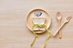 Viktskala med den hälsosamma skivan av bröd och mätabandet på den wood plattan för att banta vikt arkivfoto