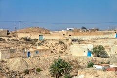 Vila árabe no deserto de Tunísia com as casas da areia e das portas azuis Imagem de Stock