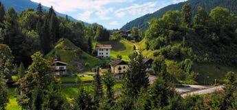 Vila alpina sob as montanhas no nascer do sol imagem de stock royalty free