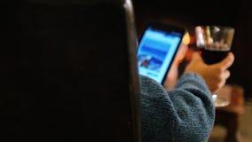 Vila bekvämt Kvinnan med ett exponeringsglas av vin på minnestavlan läser nyheterna om branden arkivfilmer