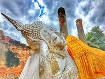 Vila Buddha avbilda framme av den gamla tegelstenväggen mot blå himmel Arkivfoton
