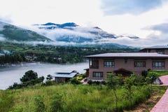 Vila butanesa perto do rio em um dia nevoento em Punakha, Butão fotos de stock royalty free