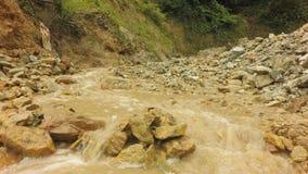 Vila da mineração do ouro em Equador do sul com o rio pequeno que flui no primeiro plano filme