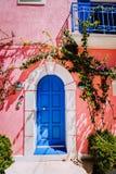 Vila de Assos O lilás tradicional coloriu a casa grega com da porta e do fucsie as flores azuis brilhantes da planta ao redor Kef fotos de stock