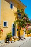 Vila de Assos O rosa tradicional coloriu a casa grega com a porta e as janelas azuis brilhantes Flores da planta de Fucsia em tor foto de stock royalty free
