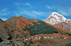 Vila de Kazbegi e igreja de trindade nas montanhas Fotos de Stock Royalty Free