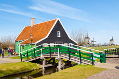 Vila de Zaanse Schans, Holanda, casas verdes e moinhos de vento contra o céu nebuloso azul Imagem de Stock