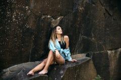 Vila efter långt ha fotvandrat för väg Den nätta kvinnan kopplar av i berg på idyllisk sommardag kvinnan sitter på vaggar på natu arkivfoton