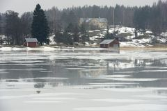 Vila em Finlandia na costa de um lago congelado imagens de stock royalty free