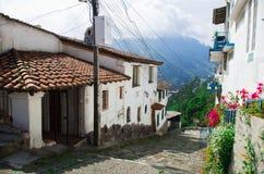 A vila encantador encontrou Quito exterior Equador com a estrada de Bridgestone que conduz para baixo para abobadar a torre do co Imagem de Stock Royalty Free