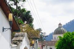 A vila encantador encontrou Quito exterior Equador com a estrada de Bridgestone que conduz para baixo para abobadar a torre do co Imagem de Stock