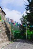 A vila encantador encontrou Quito exterior Equador com a estrada de Bridgestone que conduz para baixo para abobadar a torre do co Fotos de Stock