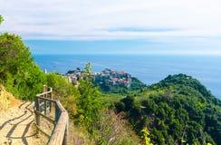 Vila italiana típica tradicional de Corniglia com as casas coloridos coloridas das construções no penhasco da rocha e na Genoa Gu foto de stock royalty free