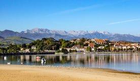 Vila litoral refletida na água, com barcos de pesca e montanhas no fundo imagens de stock royalty free