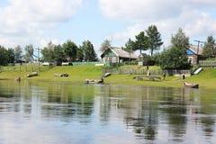Vila na costa de um rio Imagens de Stock