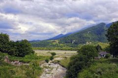 Vila na paisagem das montanhas com rio Fotos de Stock