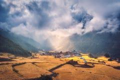 A vila no monte iluminou-se por um raio de sol no por do sol Imagens de Stock Royalty Free