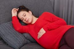 Vila och pregancybegreppet Tar den gravida nätta kvinnan för brunetten ta sig en tupplur på eftermiddagen, bär tillfällig kläder, fotografering för bildbyråer