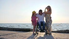 Vila ogiltigt med frun och dottern i panelljuset, farsan, barnet och modern som kramar sig, glad familj på bakgrund arkivfilmer